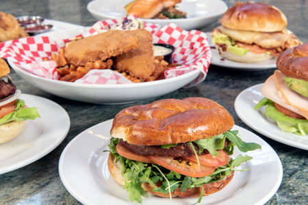 Full table of a variety of restaurant dishes to choose from with vegan burger in the center.