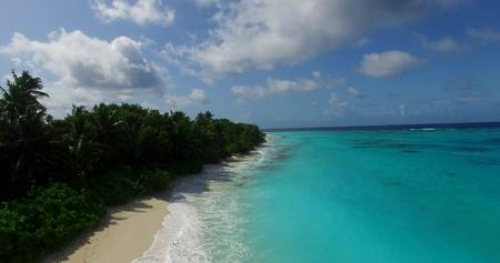 Maldives beautiful beach background white sandy tropical paradise island with blue sky sea water ocean 4k aerial drone flying helicopter shot