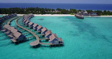 Aerial flying drone view of Maldives white sandy beach on sunny tropical paradise island with aqua blue sky sea water ocean 4k luxury 5 star resort hotel water bungalow hut relaxing holiday vacation