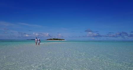 flying kiss: Aerial flying drone view of Maldives white sandy beach 2 people young couple man woman romantic love on sunny tropical paradise island with aqua blue sky sea water ocean 4k Stock Photo