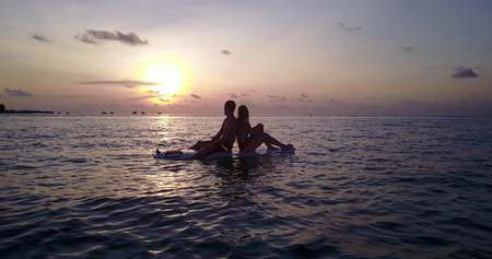 man flying: v04089 Aerial flying drone view of Maldives white sandy beach 2 people young couple man woman paddleboard rowing sunset sunrise on sunny tropical paradise island with aqua blue sky sea water ocean 4k Stock Photo