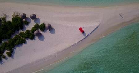 v04312 Aerial flying drone view of Maldives white sandy beach on sunny tropical paradise island with aqua blue sky sea water ocean 4k Stock Photo