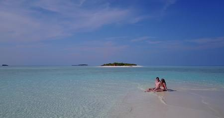 flying kiss: View of tropical paradise island Maldives beach with 2 young couple swimming on a sunny day.