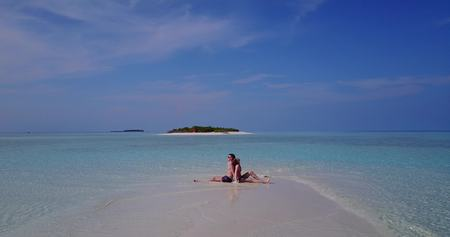flying kiss: Aerial flying drone view of Maldives white sandy beach 2 people young couple man woman romantic love on sunny tropical paradise island with aqua blue sky sea water ocean