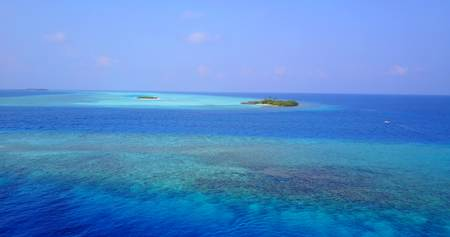 Aerial flying drone view of Maldives white sandy beach on sunny tropical paradise island with aqua blue sky sea water ocean Imagens