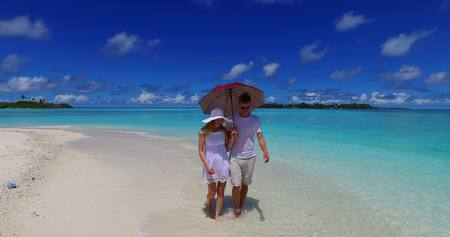enamorados besandose: Maldives white sandy beach 2 people a young couple man woman walking together in love on sunny tropical paradise island with aqua blue sky sea water ocean 4k Foto de archivo