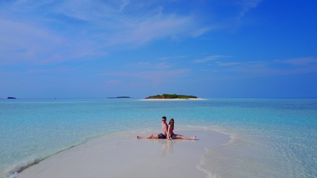 flying kiss: Aerial flying drone view of Maldives white sandy beach 2 people young couple man woman romantic love on sunny tropical paradise island with aqua blue sky sea water ocean 4k. Stock Photo