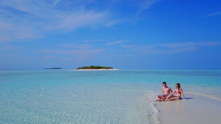 flying kiss: P00084 Aerial flying drone view of Maldives white sandy beach 2 people young couple man woman romantic love on sunny tropical paradise island with aqua blue sky sea water ocean 4k Stock Photo