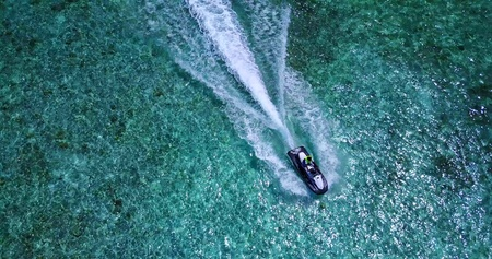 Aerial flying drone view of Maldives white sandy beach jetski riding sunny tropical paradise island with aqua blue sky sea water ocean
