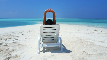 Maldives white sandy beach young woman relaxing on sunbed on sunny tropical paradise island with aqua blue sky sea ocean Stock Photo
