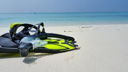 Maldives white sandy beach fins snorkel mask scuba flippers on sunny tropical paradise island with aqua blue sky sea ocean 4k Stock Photo