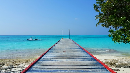Maldives white sandy beach jetty on sunny tropical paradise island with aqua blue sky sea ocean 4k