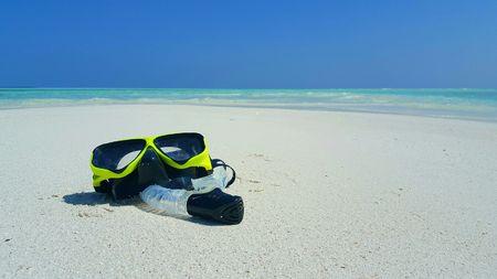flippers: Las aletas de la playa de arena blanca de Maldivas aletas del equipo de submarinismo en la isla soleada del paraíso tropical con aqua cielo azul mar océano 4k Foto de archivo