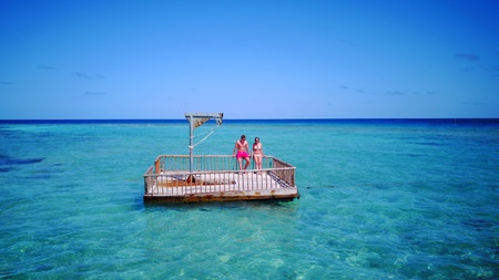 young couple man woman relaxing on sunny tropical paradise island with aqua blue sky sea water ocean floating pontoon