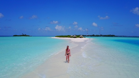 young woman walking on sunny tropical paradise island with aqua blue sky sea water ocean Stock Photo