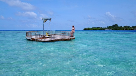 young woman relaxing on floating pontoon jetty sunbathing on sunny tropical paradise island with aqua blue sky sea water ocean