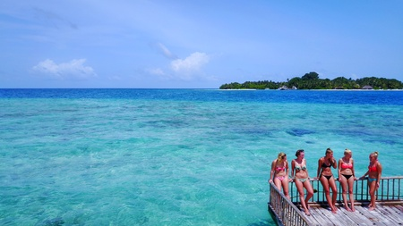 5 person happy young woman relaxing on floating pontoon jetty sunbathing on sunny tropical paradise island with aqua blue sky sea water ocean