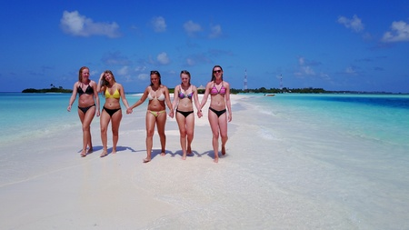 5 people young woman relaxing sunbathing together on sunny tropical paradise island with aqua blue sky sea water ocean