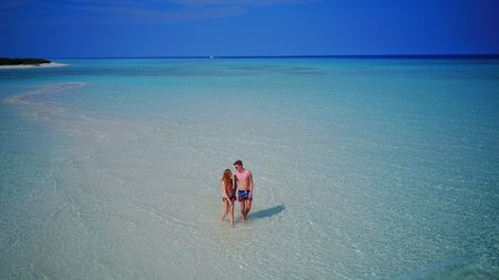 young couple man woman romantic love on sunny tropical paradise island with aqua blue sky sea water ocean