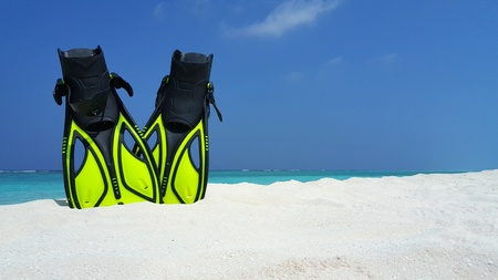 Maldives white sandy beach fins snorkel mask scuba flippers on sunny tropical paradise island with aqua blue sky sea ocean