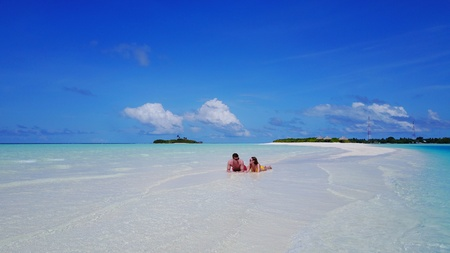 flying kiss: young couple man woman romantic love on sunny tropical paradise island with aqua blue sky sea water ocean