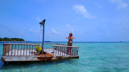 happy young woman relaxing on floating pontoon jetty sunbathing on sunny tropical paradise island with aqua blue sky sea water ocean