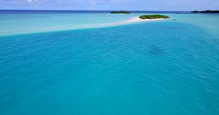 Maldives white sand beach tropical islands with drone aerial flying birds eye view with aqua blue sea water and sunny sky Stock Photo