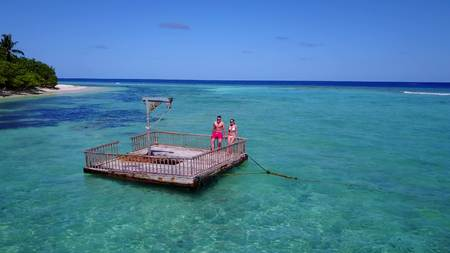 2 young people couple romantic sunbathing on pontoon with aerial view in beautiful clear aqua blue sea water Stock Photo