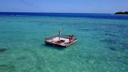 Two young people couple romantic sunbathing on pontoon with aerial view in beautiful clear aqua blue sea water Imagens