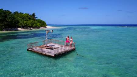 Young people couple romantic sunbathing on pontoon with aerial view in beautiful clear aqua blue sea water Imagens