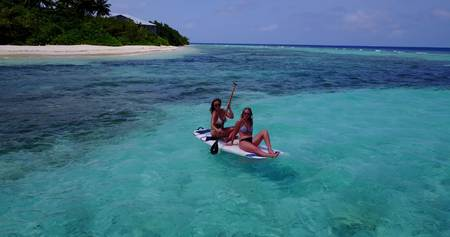 two pretty young girls on a paddle board with aerial view in warm blue sea water