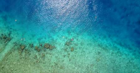 water texture breaking and crashing with drone aerial flying view of aqua blue and green clear sea ocean Stock Photo