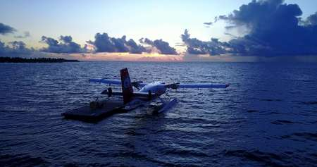 seaplane at sunset sunrise in maldives with view from aerial drone on purple blue sea ocean water and sky