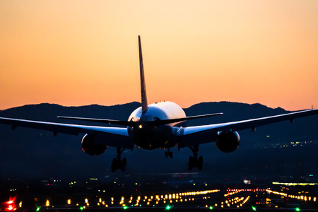 runway: Airplane landing to the airport at dusk Stock Photo