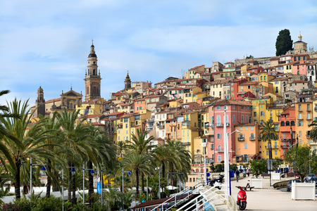 menton: Promenade of Menton with palm trees and colorful building in background Stock Photo