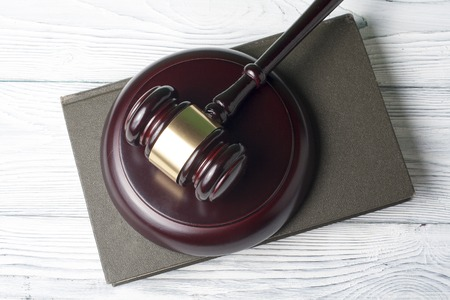 Book with wooden judges gavel on table Stock Photo