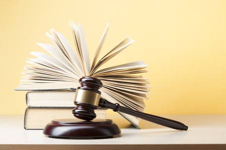 enforcement: Book with wooden judges gavel on table in a courtroom or enforcement office