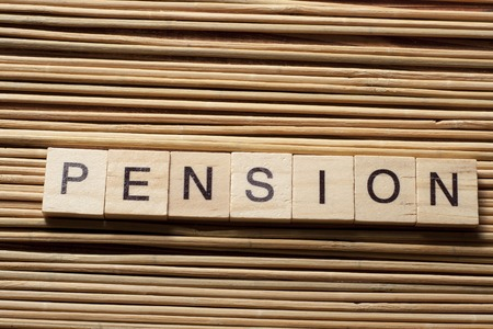 pension: PENSION word written on wooden block at table