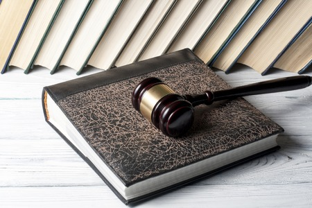 Book with wooden judges gavel on table in a courtroom or enforcement office
