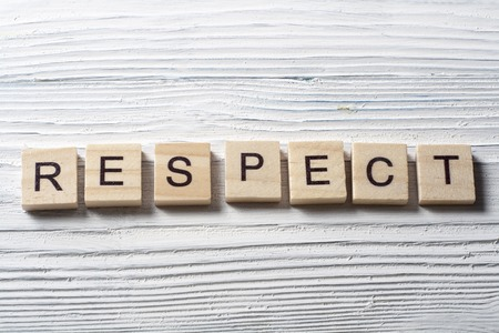 dignity: RESPECT word written on wood block ta wooden background.