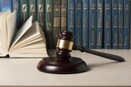 Concepto de la ley - libro con los jueces martillo de madera sobre la mesa en una oficina de sala o la ejecución Foto de archivo