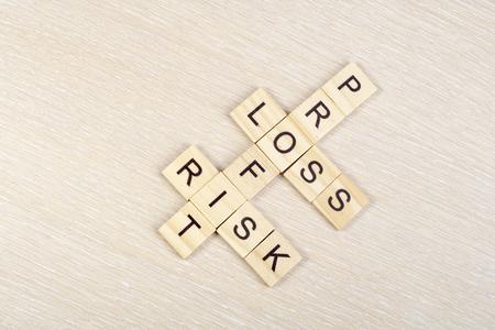 perdidas y ganancias: Beneficios, la p�rdida y bloques de palabras cruzadas del riesgo en la mesa. Vista superior.