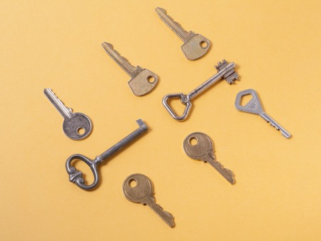 Set of assorted different keys on wooden background.