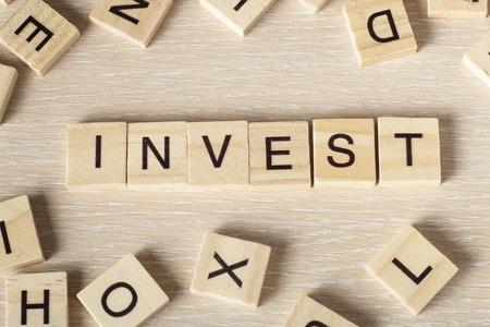 non stock: invest word written on wood block. Wooseb Abc