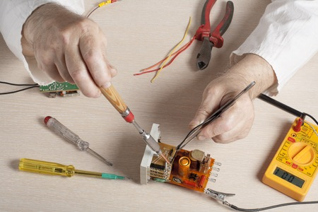 manual test equipment: Hand of electrician with multimeter probe at  electrical switchgear cabinet. Engineering tools.