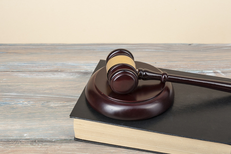 Law concept - Book with wooden judges gavel on table in a courtroom or enforcement office.Copy space for text. Stock Photo