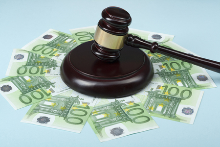 Law concept. Artistic concept on corruption in society. Judge gavel and cash money on wooden table.