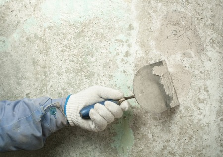 Construction and renovation concept. Hand of worker with plastering tools.