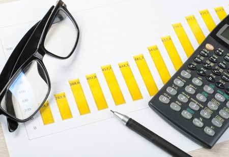 Home savings, budget concept. Chart, pen, calculator and glasses on wooden office desk table