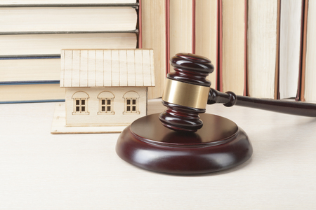 Law concept. Miniature house, books with wooden judge gavel on table in a courtroom or enforcement office.